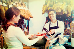 Young cheerful brunette choosing iberico and serrano jamon. And smiling Royalty Free Stock Photos
