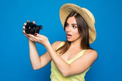 Young cheerful brunette female tourist photographer is smiling on the blue background. She is excited and holding camera, wearing. Young cheerful brunette female Royalty Free Stock Image