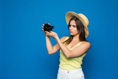 Young cheerful brunette female tourist photographer is smiling on the blue background. She is excited and holding camera, wearing. Young cheerful brunette female Stock Photography