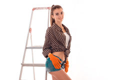 Young cheerful brunette woman in uniform makes renovation with ladder looking at the camera and smiling isolated on Stock Photo
