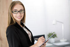 Young cheerful business woman standing with clipping board Stock Photo