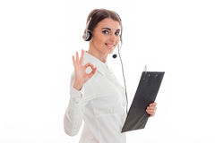 Young cheerful business woman in uniform with headphones and microphone looking at the camera and showing OK isolated on Royalty Free Stock Photography