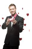 Young cheerful businessman holding red gift Stock Photography