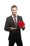 Young cheerful businessman holding red heart Stock Images