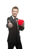 Young cheerful businessman holding red heart Stock Photos