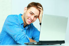 Young cheerful businessman sitting at the table with laptop Royalty Free Stock Photography