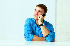 Young cheerful businessman talking on the phone and looking up at copyspace Royalty Free Stock Images