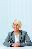 Young cheerful businesswoman in casual cloth sitting at the table Royalty Free Stock Images