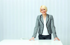 Young cheerful businesswoman in casual cloth standing at her workplace Royalty Free Stock Photography