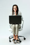 Young cheerful businesswoman with laptop sitting on chair Stock Images