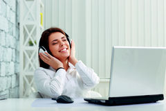 Young cheerful businesswoman listening music in headphones Stock Photography