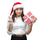 Young cheerful businesswoman in santa hat holding christmas gift Royalty Free Stock Image