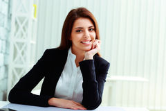 Young cheerful businesswoman sitting at the table on her workplace Stock Images
