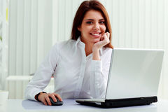 Young cheerful businesswoman sitting at the table on her workplace Stock Photography