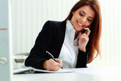 Young cheerful businesswoman talking on the phone and writing notes