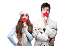 Young cheerful casual couple holding red hearts Royalty Free Stock Image
