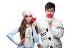 Young cheerful casual couple holding red hearts Royalty Free Stock Photo