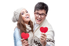 Young cheerful casual couple holding red hearts Royalty Free Stock Images
