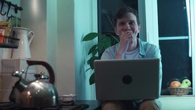 Young man typing on computer sitting at kitchen while kettle boiling on stove stock video