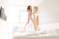 Young cheerful woman jumping on bed and playing with pillow. Young cheerful caucasian woman in pajamas jumping on bed with pillow and smiling at home Royalty Free Stock Photo