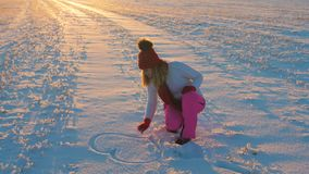 Woman At Sunset on a Winter Day In the Snow painting with Hand Heart 4k stock video