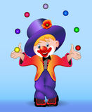 Young cheerful clown juggles balls Stock Photography