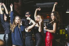 Young cheerful company of friends at the club bar dancing having royalty free stock photography