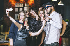 Young cheerful company of friends in the club bar having fun and Royalty Free Stock Photography