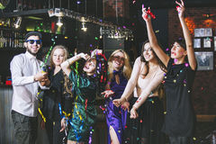 Young cheerful company of friends in the club bar having fun wit. H multi-colored confetti and crackers celebrate the holidays stock photography