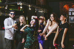 Young cheerful company of friends in the club bar having fun wit. H multi-colored confetti and crackers celebrate the holidays royalty free stock photo