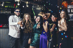 Young cheerful company of friends in the club bar having fun wit. H multi-colored confetti and crackers celebrate the holidays stock photos