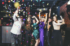 Young cheerful company of friends in the club bar having fun wit. H multi-colored confetti and crackers celebrate the holidays stock images