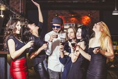 Young cheerful company of friends in the club bar having fun wit. H alcohol in hand celebrate the holidays royalty free stock image