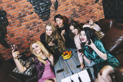 Young cheerful company of friends in a restaurant having fun tak Stock Photo