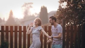 Young cheerful couple on the backyard, having fun together on sunset. Cheerful man and woman dancing outside. Happy active male and female spending weekend on stock video