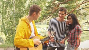 Young cheerful couple enjoying listening to their friend`s playing the guitar stock video