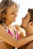Young cheerful couple having fun on the beach Stock Photos