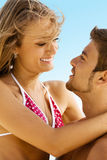 Young cheerful couple having fun on the beach Stock Photography