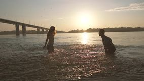 Young cheerful couple having fun in the water on a hot summer evening. They play with water near the city bridge stock video