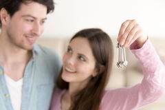 Young cheerful couple holding new house keys, real estate mortga. Smiling women showing keys of apartment, looking at her husband. Young defocused couple Royalty Free Stock Photography
