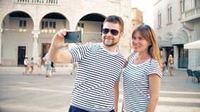 Young cheerful couple making selfie on vacation. Young happy couple making selfie stock footage