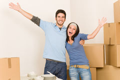 Young cheerful couple moving into new home. Moving new home young cheerful couple unpacking cardboard boxes together Stock Photos