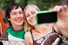 Young cheerful couple photographing themselves. Happy young couple taking photo of themselves royalty free stock images