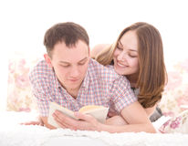 Young cheerful couple reading a book Stock Images