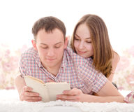 Young cheerful couple reading a book Royalty Free Stock Photos