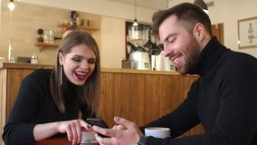 A young cheerful couple rest in a coffee shop and look at the phone screens. stock footage