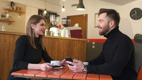 A young cheerful couple rest in a coffee shop and look at the phone screens. Young man and woman sitting during lunch in a coffee shop, drink coffee and discuss stock footage