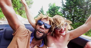Young cheerful couple singing while driving in convertible, graded. Young cheerful interracial couple listening to music and singing while driving in convertible stock video