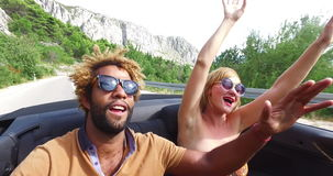Young cheerful couple singing while driving in convertible. Young cheerful interracial couple listening to music and singing while driving in convertible car stock video