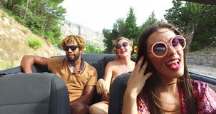Young cheerful couple singing while driving in convertible. Young cheerful interracial couple listening to music and singing while driving in convertible car stock video footage